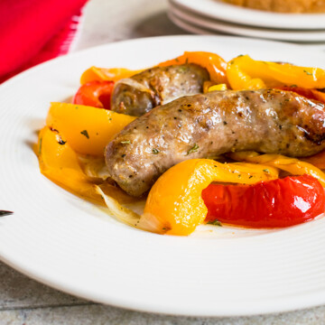 sausages, sliced peppers on white plate