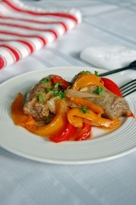 Sausage and Peppers on a plate with fork and knife