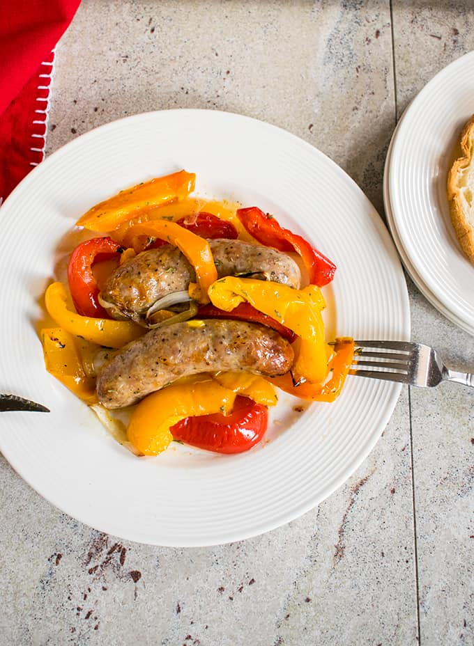 overhead view of sausages, peppers, onions on white plate with fork, knife