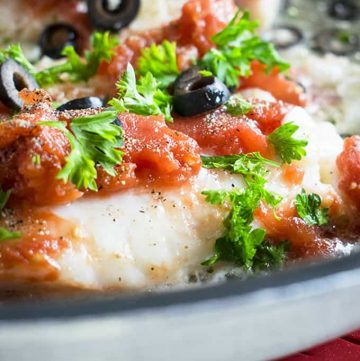 skillet of sauteed cod topped with tomatoes, parsley and olives
