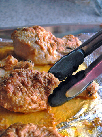 Tongs going to pick up a Parmesan Chicken Drumstick with Garlic Butter