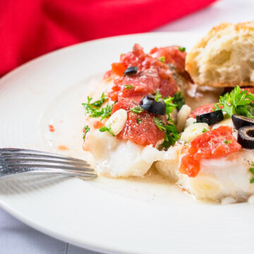 Sauteed Cod with tomatoes, parsley and olives on a plate with fork