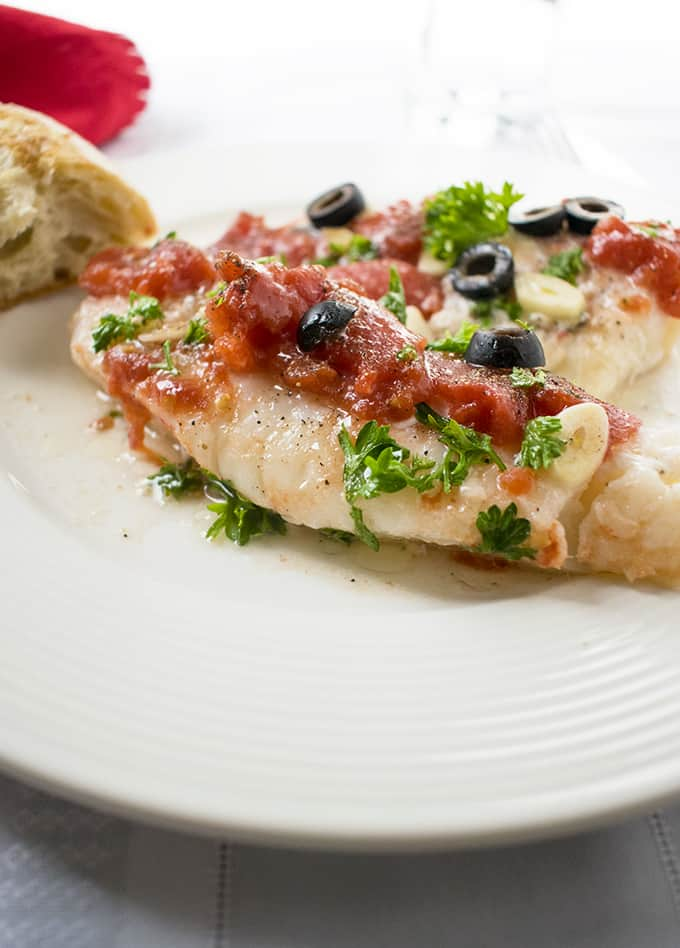 Photo of Sauteed Cod with Tomatoes in a Dish with a Chunk of Bread
