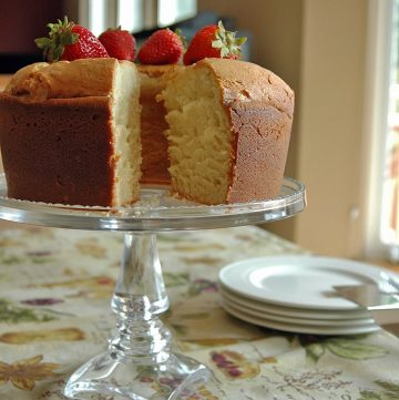 Pound cake with piece taken from it on a cake stand