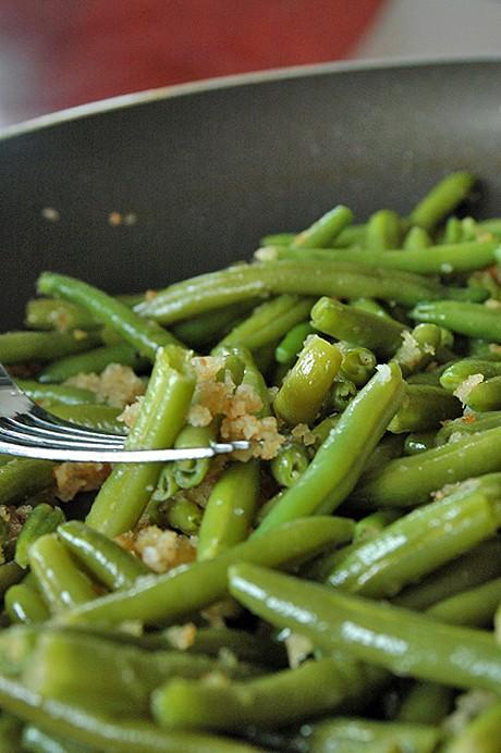 fork in pan of green beans with bread crumbs