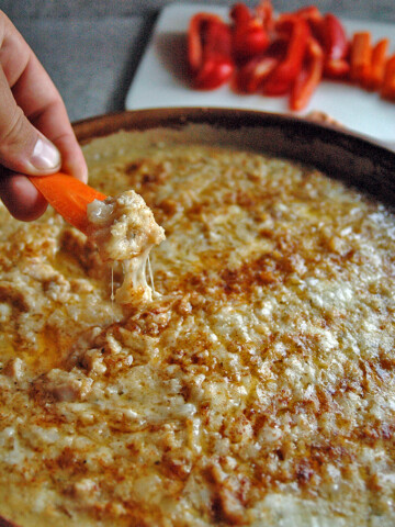 Hand dipping a carrot slice in Meatless Clams Casino Dip