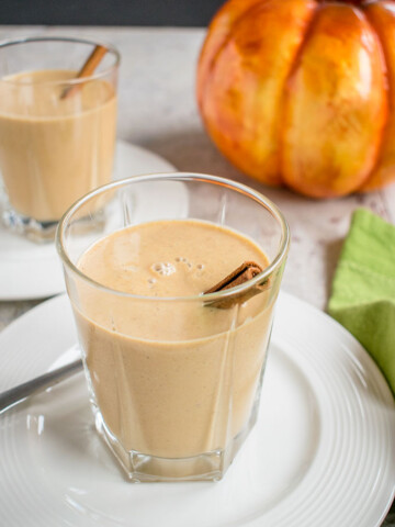 two glasses of pumpkin smoothies with cinnamon sticks on plates
