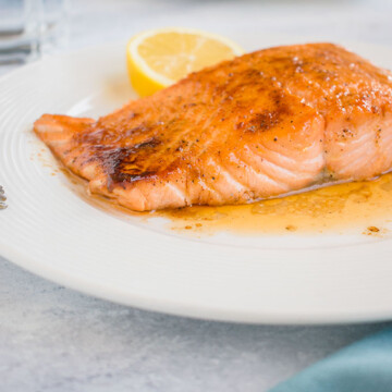 ten minute maple-glazed salmon on a plate with a slice of lemon