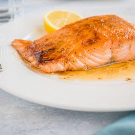 Photo of 10-Minute Maple-Glazed Salmon on plate with slice of lemon