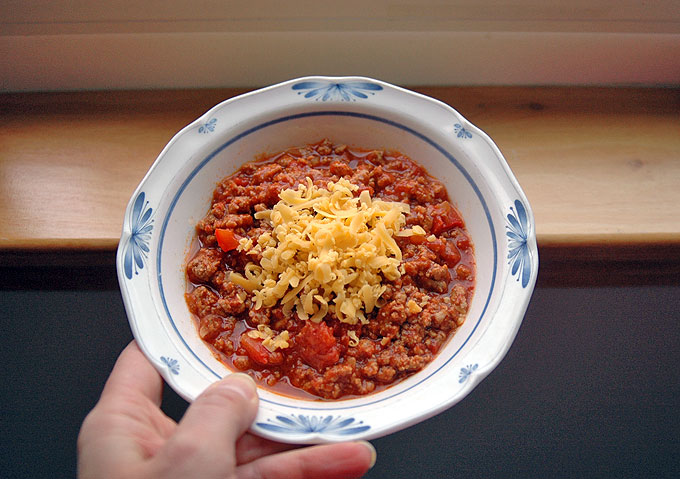 hand holding a bowl of Turkey BBQ Chili with Red Peppers