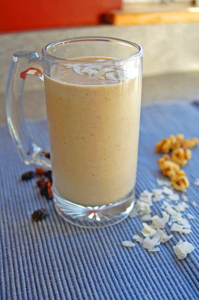 glass mug filled with Banana Nut Oatmeal Raisin Smoothie with Coconut, raisins, walnut halves, shaved coconut