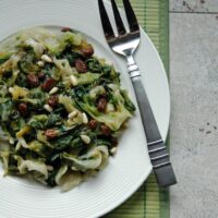 overhead view of Escarole with Raisins and Pine Nuts on a plate with serving fork