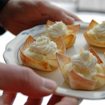 hands holding a plate of coconut cream pie cups
