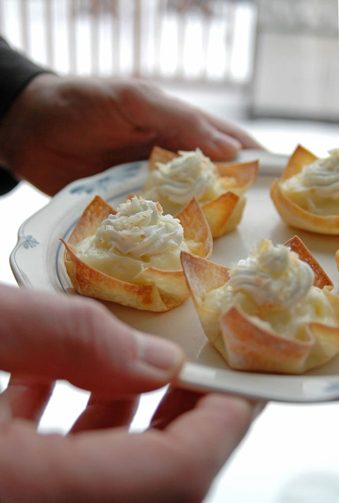 hands holding plate of coconut cream pie cups