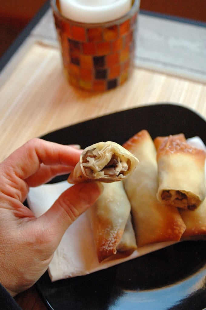 hand holding a Crispy Mushroom Onion Feta Roll with bite taken out