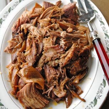 overhead shot of slow cooker Carolina pulled pork on a platter with a serving fork