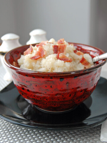 spoon in bowl of mashed turnips with bacon