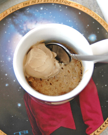 overhead view of White Chocolate Macadamia and Coconut Mug Cookie with spoon inside