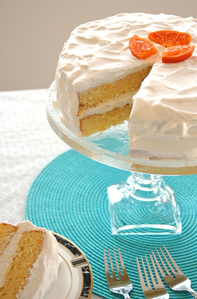 Orange Torte with Whipped Cream with piece taken out on a cake stand