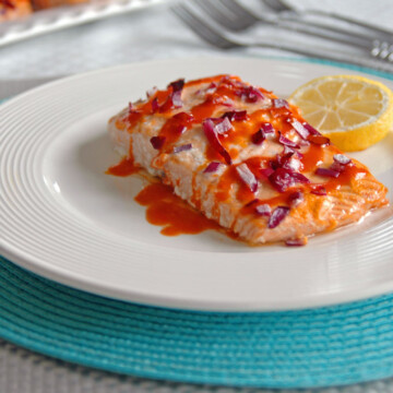 Buffalo Salmon with Roasted Red Peppers on a plate with lemon