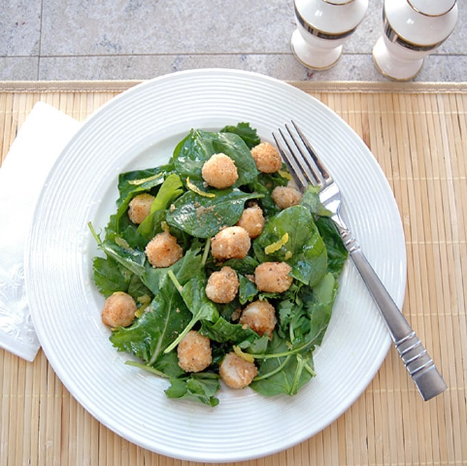 overhead view of breaded scallops over salad with lemon vinaigrette on a plate with fork