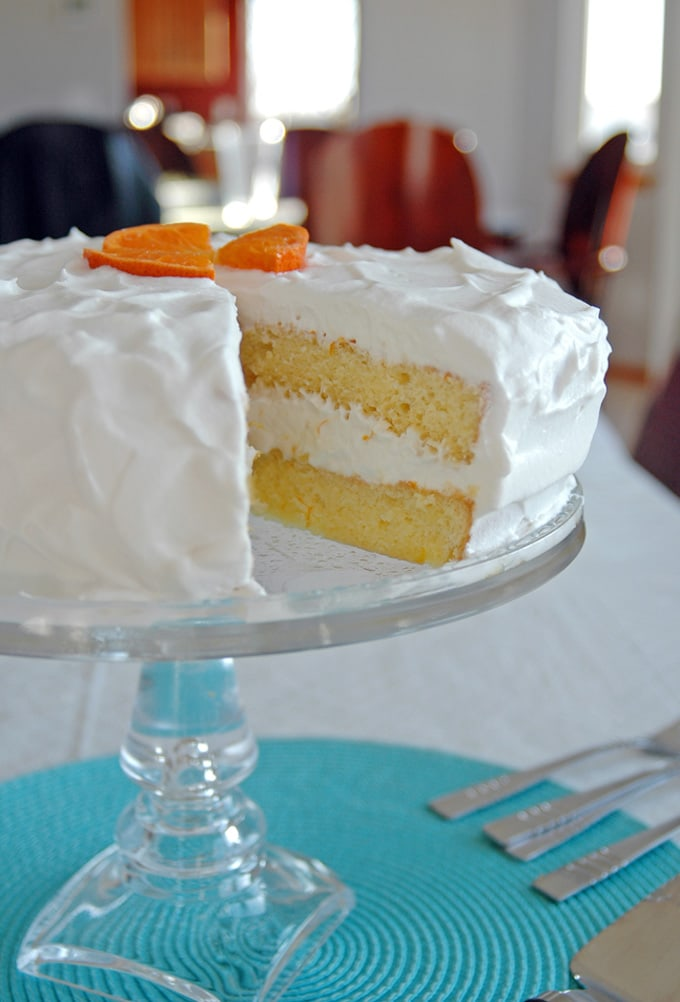 side view of a slice taken out of Orange Torte with Whipped Cream