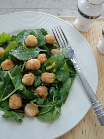 breaded scallops over salad with lemon vinaigrette on a plate with fork