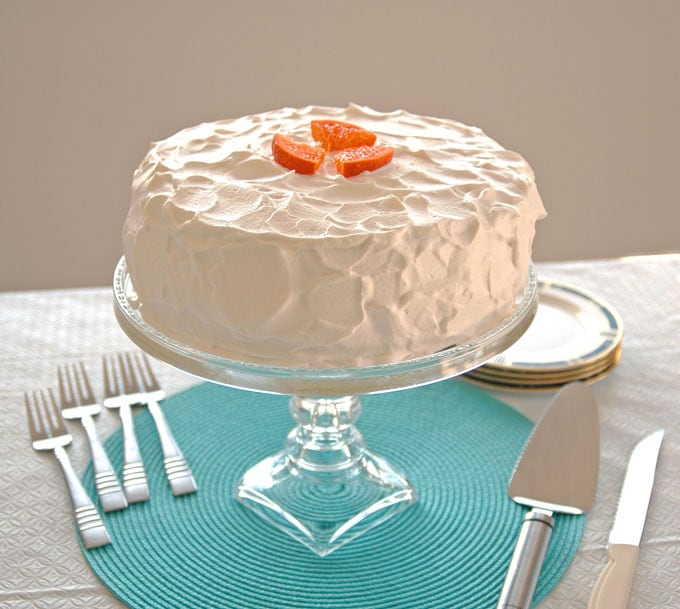 Orange Torte with Whipped Cream on stand, pie server, forks