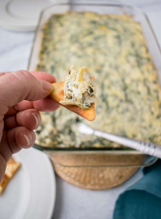 Photo of hand holding pita cracker with Asiago Spinach and Artichoke Dip