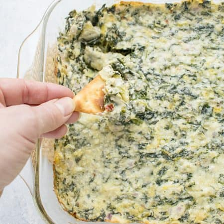 Overhead photo of hand holding a pita cracker topped with Asiago Spinach and Artichoke Dip over the baking dish