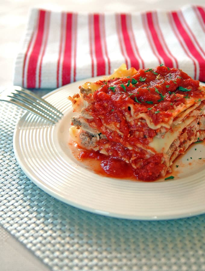 piece of traditional lasagna on a plate with fork