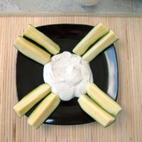 ranch dressing on a black plate with sliced zucchini