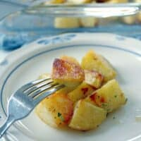 fork taking a piece of oven roasted potato with seasonello from the plate