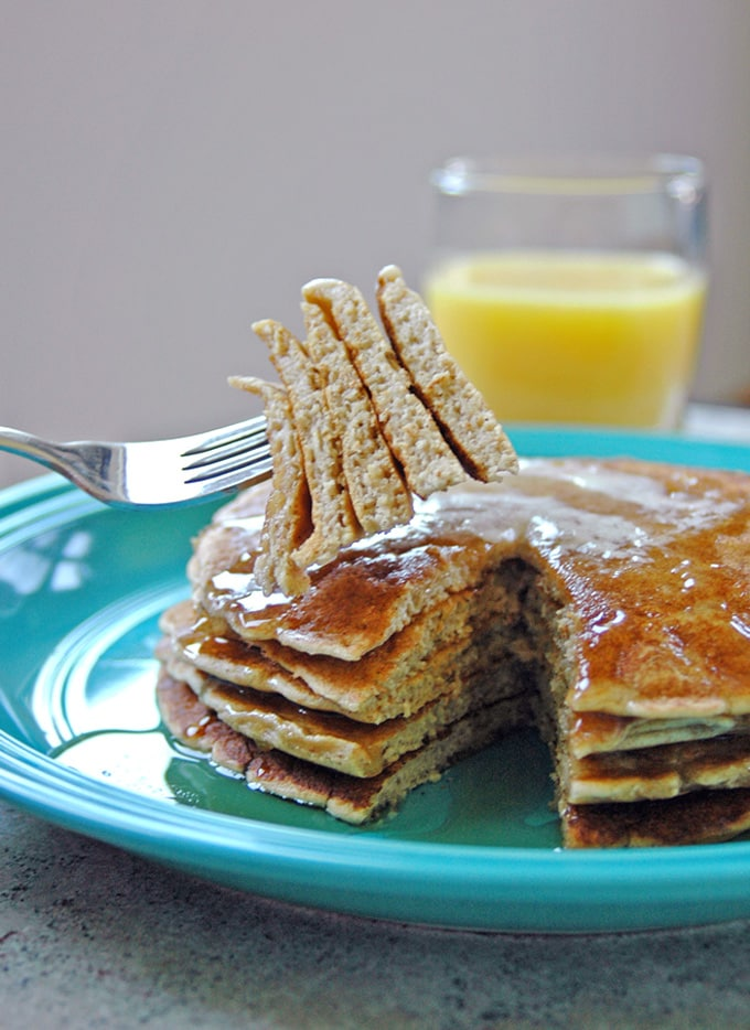 stack of Cinnamon Almond Multigrain Pancakes with a forkful being taken