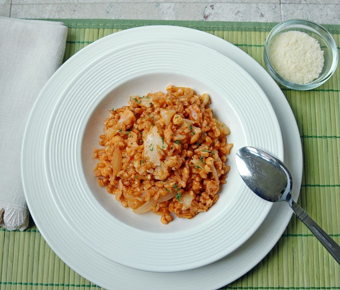 overhead view of One Pot Farro with Cauliflower and Onions in a bowl with spoon