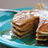stack of Cinnamon Almond Multigrain Pancakes on a plate with a piece cut out