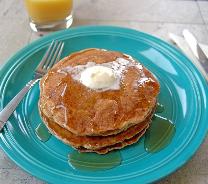 stack of Cinnamon Almond Multigrain Pancakes covered in butter and syrup on a plate with a fork