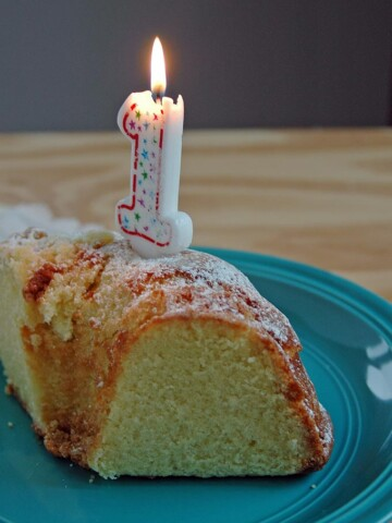 Slice of cake with a burning 1 candle on it
