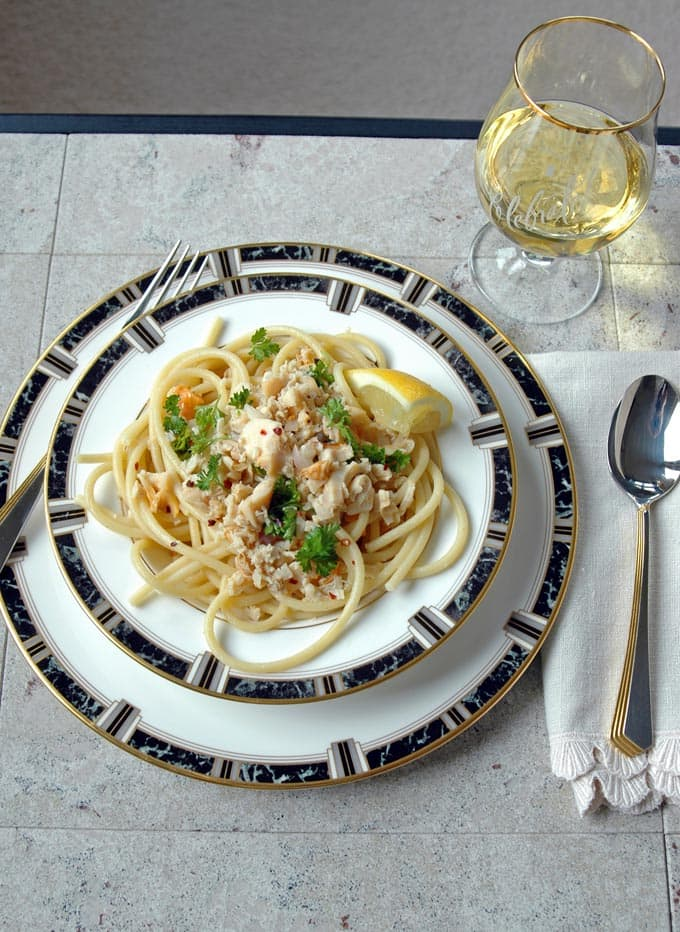 overhead view of Bucatini with Clams and White Wine in a bowl on a plate with a fork, spoon and white wine