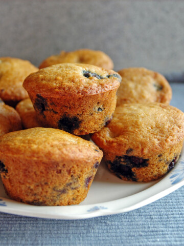 Whole Wheat Blueberry Muffins stacked together on a plate