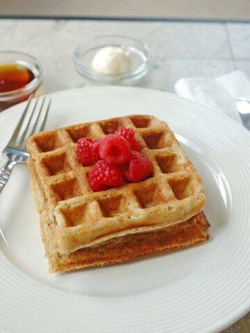 2 Buttermilk Whole Grain Waffles stacked on a plate with raspberries, fork, butter and syrup