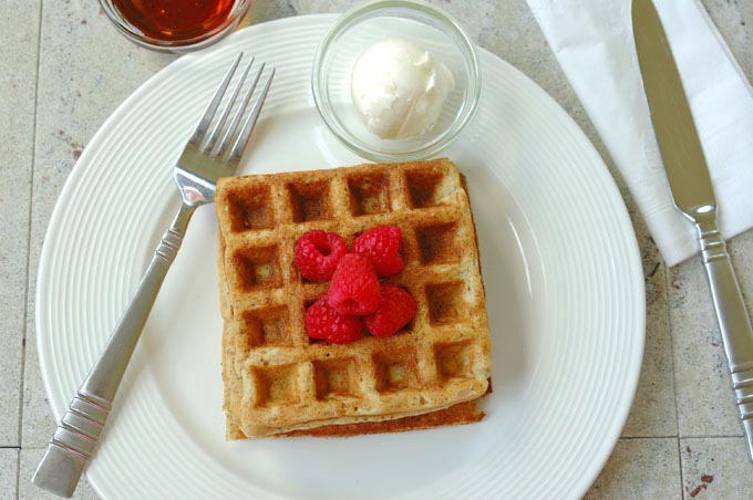 overhead view of Buttermilk Whole Grain Waffles topped with raspberries on a plate with butter and fork