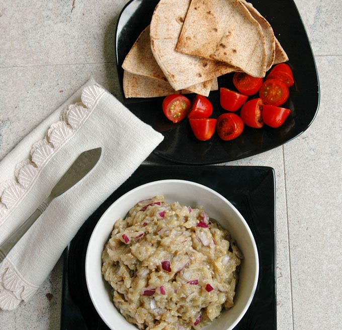 overhead view of Roasted Eggplant Dip in a bowl next to a plate with pita and small tomatoes, napkin with spreading knife