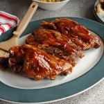 Slow Cooker BBQ Ribs on a plate with dressing brush