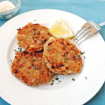 plate with three Crispy Crab Cakes and a fork, glass of butter behind