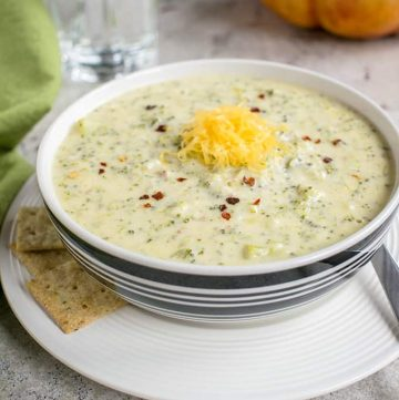 bowl of broccoli-cheddar soup on a plate with crackers