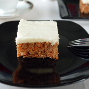 Slice of Carrot Cake with Cream Cheese Frosting on black plate