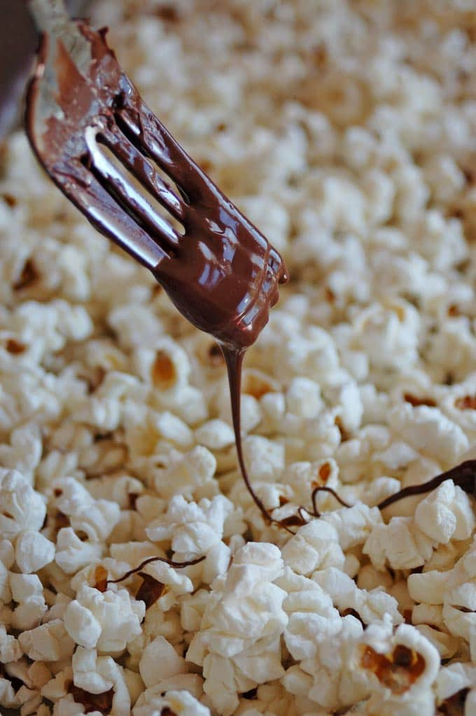 fork drizzling dark chocolate onto popcorn