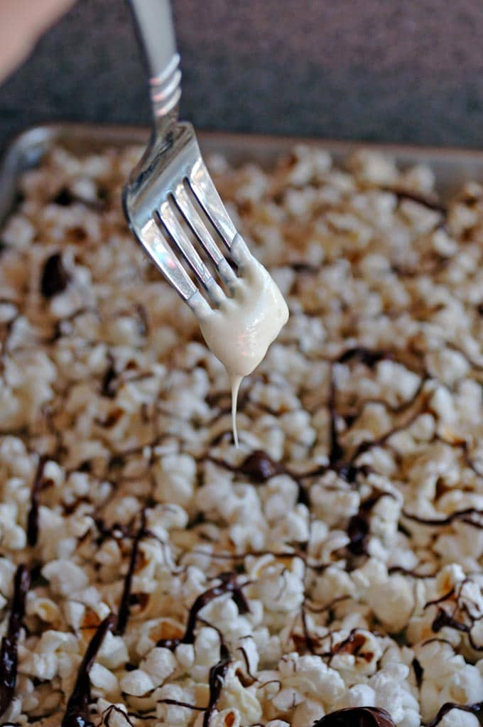 fork drizzling white chocolate onto popcorn with dark chocolate drizzle