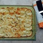 overhead view of Crispy Parmesan Potatoes with Onions and Garlic Butter in a glass pan